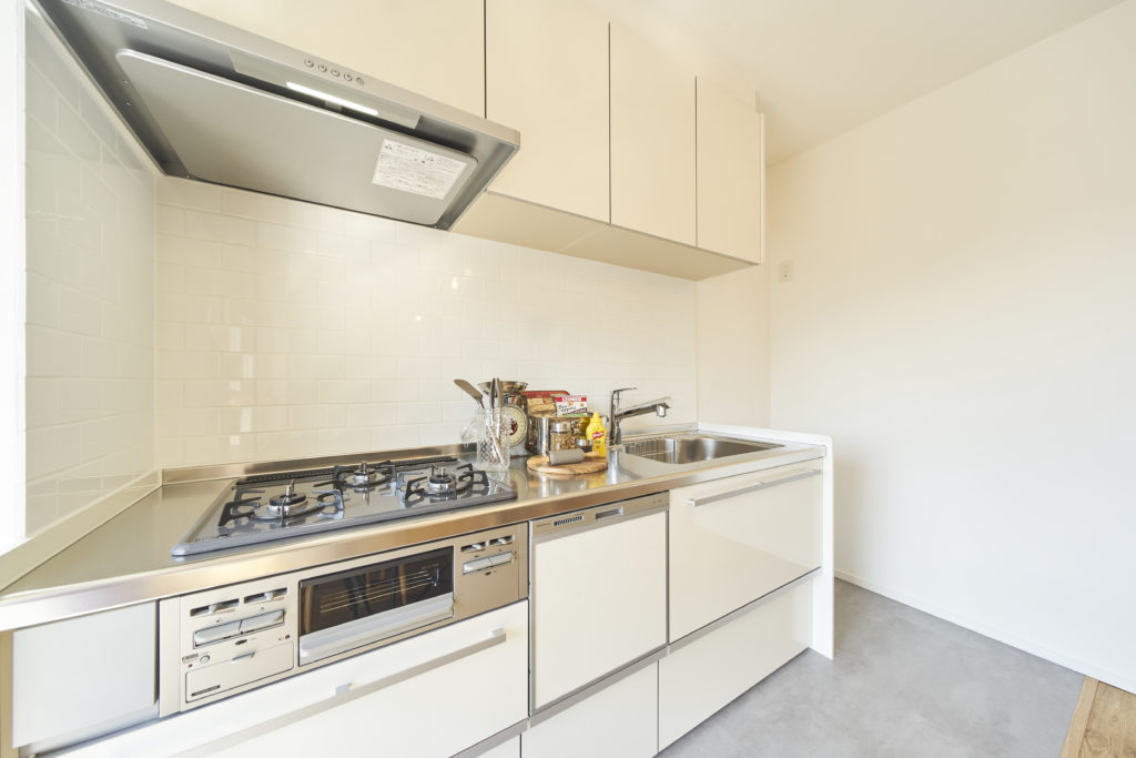白いキッチンとタイル壁の組み合わせ